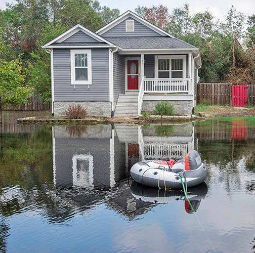 A moored rubber rescue raft in a lake formed by Hurricane Florence in the yard around a grey single-family home in North Carolina.
