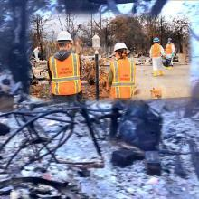 Fire recovery employees superimposed over burned-out debris from the fires.