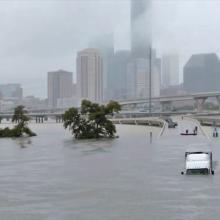 Floodwaters against the downtown Houston, Texas skyline half covering a tractor-trailer on an exit ramp angled upwards. People are gathered on the ramp.