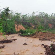A muddy river in Puerto Rico with washed-out riverbanks on the opposite side.