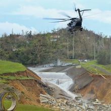A Navy MH53 helicopter places a barrier down to strengthen the broken dam, Oct. 5, 2017 at Guajataca Dam, Isabela, Puerto Rico. The Department of Defense is conducting on-going missions to rebuild and assist the citizens of Puerto Rico. (U.S. Army photo by: Pfc. Deomontez Duncan)